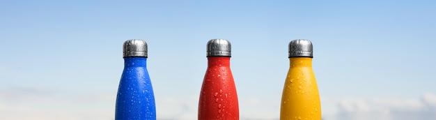 Zestaw trzech termosów wielokrotnego użytku ze srebrną zatyczką, spryskanych wodą. kolor niebieski, czerwony i żółty. zbliżenie na pół butelki