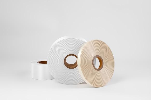 Zestaw trzech zwojów satynowej wstążki z boku na etykiety lub majsterkowanie w kolorze białym beżowym na białym tle