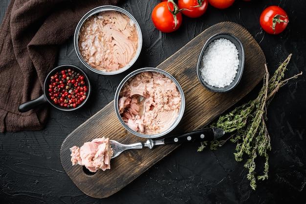 Zestaw tuńczyka białego mięsa białego bez soi w puszkach, na drewnianej desce do krojenia, na czarno