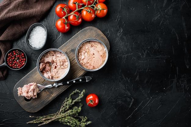 Zestaw tuńczyka włoskiego w puszkach, na drewnianej desce do krojenia, na czarno