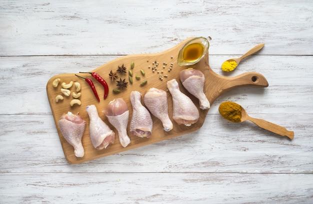 Zestaw udek z kurczaka przed gotowaniem. udka z kurczaka na desce do krojenia.