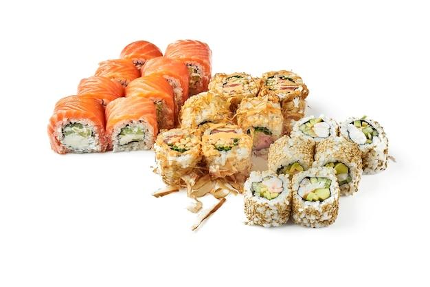 Zestaw uramaki sushi california z krewetką, philadelphia z łososiem, bonito z tuńczykiem. klasyczna kuchnia japońska. dostawa jedzenia. na białym tle.