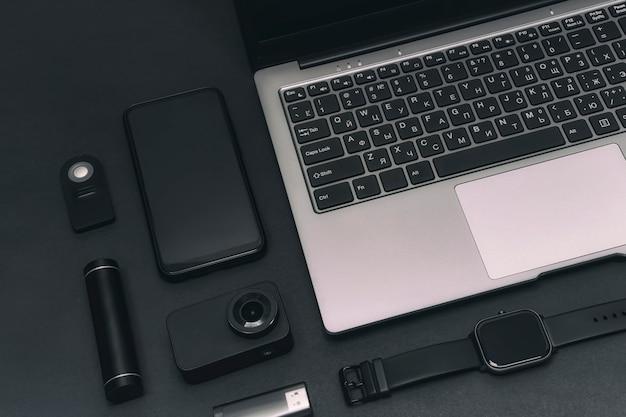 Zestaw urządzeń multimedialnych. laptop z kamerą sportową, smartfonem, smart zegarkiem i power bankiem z pendrive'em na czarnym tle.