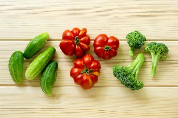 Zestaw warzyw. pomidory, ogórki i brokuły na jasnym tle drewniane.