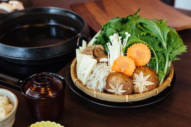 Zestaw warzyw sukiyaki zawierający kapustę, fałszywe pak choi, marchew, shiitake, enokitake i tofu.