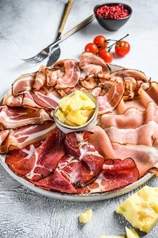Zestaw wędlin peklowanych na zimno szynka, szynka prosciutto, pancetta, boczek. białe tło. widok z góry.