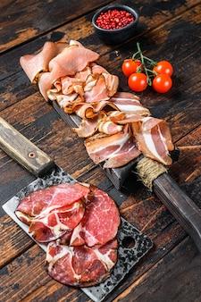 Zestaw wędlin peklowanych na zimno szynka, szynka prosciutto, pancetta, boczek. ciemne tło drewniane. widok z góry.