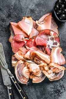 Zestaw wędlin peklowanych na zimno szynka, szynka prosciutto, pancetta, boczek. czarne tło. widok z góry.