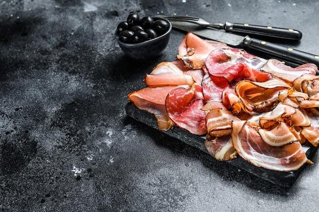 Zestaw wędlin peklowanych na zimno szynka, szynka prosciutto, pancetta, boczek. czarne tło.