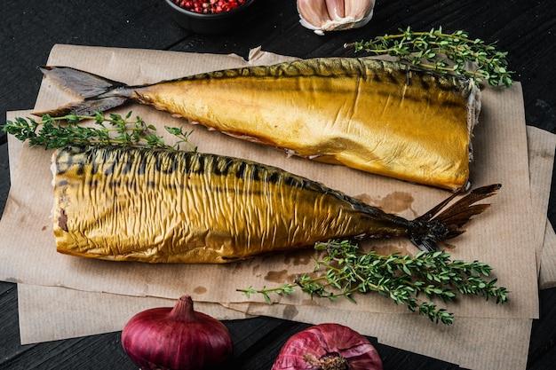 Zestaw wędzonej makreli rybnej, na czarnym tle drewnianego stołu
