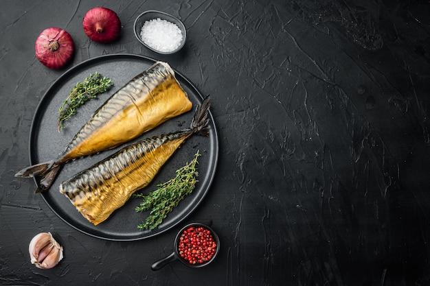 Zestaw wędzonej makreli rybnej, na czarnym tle, widok z góry płasko leżał z miejscem na kopię tekstu