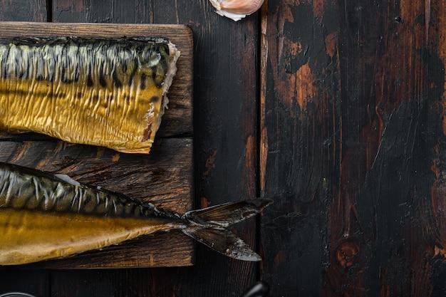 Zestaw wędzonej makreli rybnej, na starym ciemnym tle drewnianego stołu, widok z góry płasko leżał z miejscem na tekst