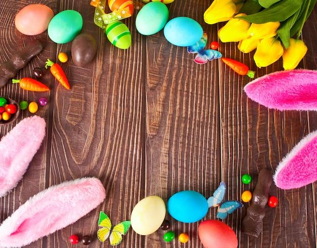 Zestaw wielkanocny z kolorowymi jajkami, tulipanami, uszami królika, marchewką na drewnianym tle. widok z góry. skopiuj miejsce.