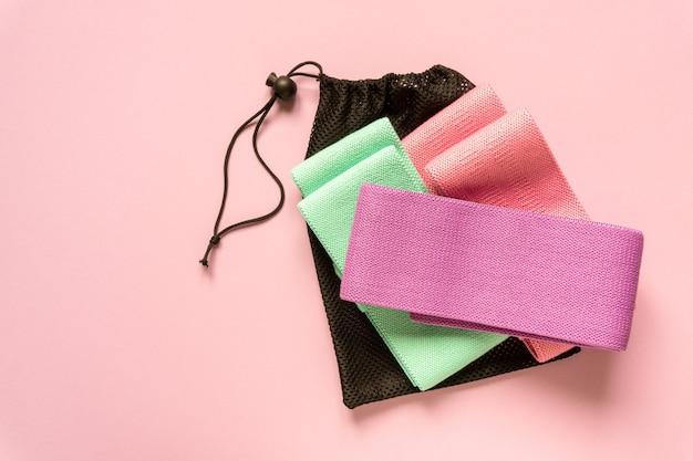 Zestaw wielobarwnych opasek fitness tkaniny na różowym tle.