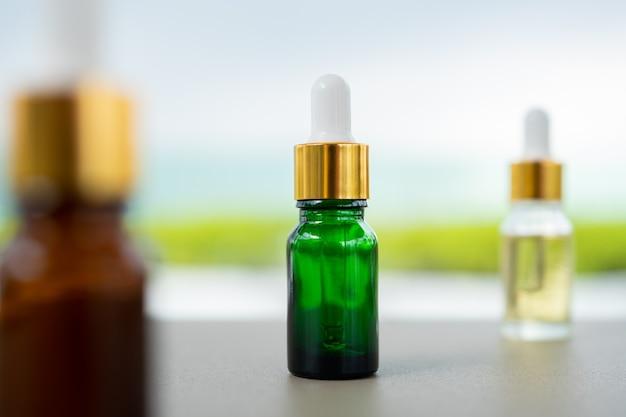 Zestaw wielokolorowych szklanych butelek z zakraplaczem na stole. koncepcja aromatycznych olejków, kosmetyków i urody skóry.