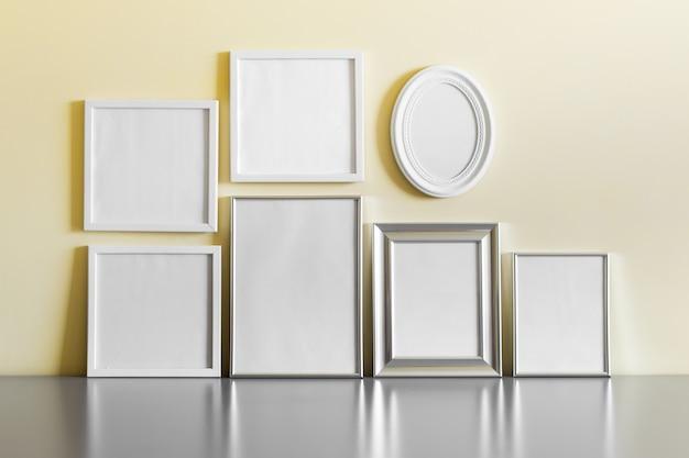 Zestaw wielu pustych metalowych srebrnych i białych drewnianych ramek na żółtej ścianie.