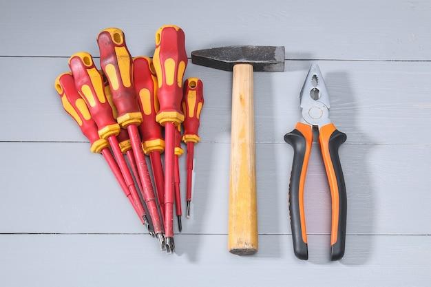 Zestaw wielu różnych czerwonych narzędzi do pracy, w tym śrubokręt młotkowy na szaro. widok z góry