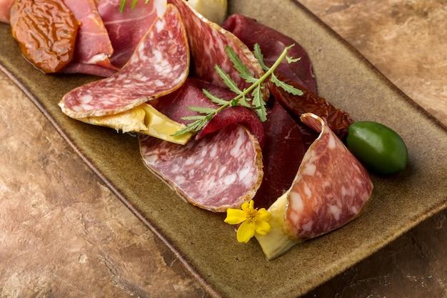 Zestaw włoski, bresaola, szynka parmeńska, salami, suszone pomidory, oliwki, cienkie plastry, danie, brązowe tło