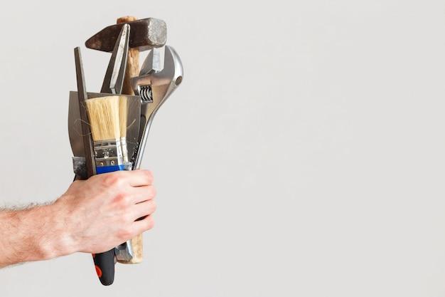 Zestaw wszystkich narzędzi do naprawy w tym samym czasie w jednej ręce mistrza. jack wszystkich branż, koncepcja uniwersalnego pracownika