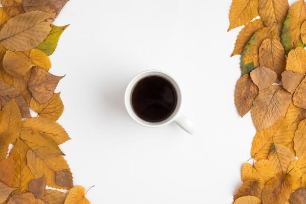 Zestaw z liści jesienią i filiżanki kawy