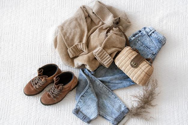 Zestaw z modną damską odzieżą jeansów i swetrem, butami i dodatkami, układany na płasko.
