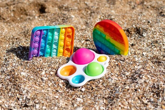 Zestaw z wielokolorowego pop it i prostego dołka pozostającego w piasku na plażyzabawka antystresowa