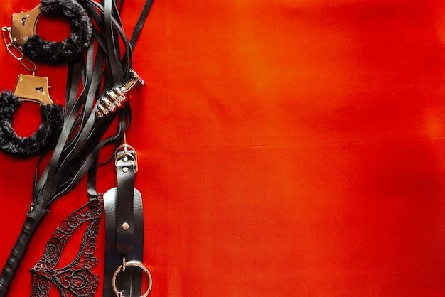 Zestaw zabawek dla dorosłych: kajdanki, korek analny, maska, bicz. miejsce na tekst