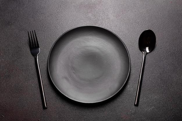 Zestaw zastawy stołowej gotowy do posiłku z miejsca kopiowania czarny. metalowy nóż, widelec, łyżka i talerz