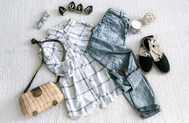 Zestaw zawiera modną odzież damską, koszulę, dżinsy i torbę z akcesoriami.