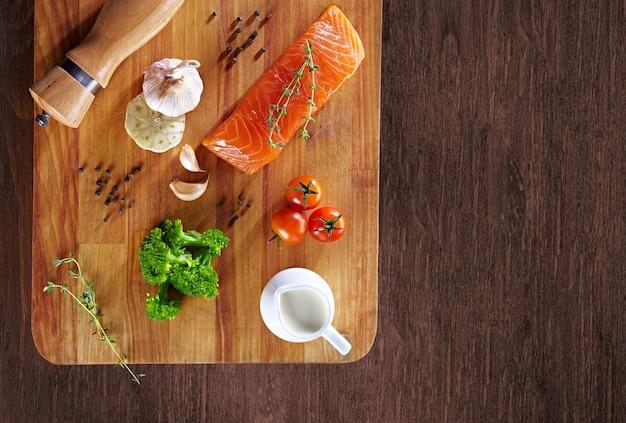 Zestaw zdrowej żywności przeciwnowotworowej na drewnianym stole. czerwona ryba łosoś, brokuły, czosnek, mleko, pieprz i pomidory rozrzucone wokół stołu. pojęcie zdrowego posiłku, widok z góry