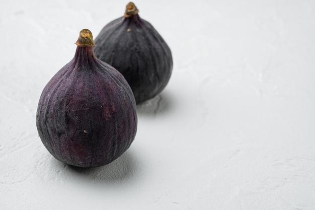 Zestaw zdrowych fig deserowych, na białym tle kamiennego stołu, z miejscem na tekst