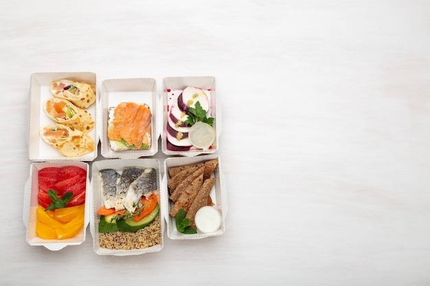 Zestaw zdrowych posiłków na cały dzień w pudełkach śniadaniowych stoi na białym stole z miejscem na kopię. pojęcie