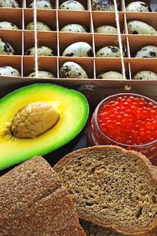 Zestaw zdrowych produktów do diety ketonowej. produkty ekologiczne. jajka przepiórcze, awokado, chleb otrębowy, kawior czerwony.