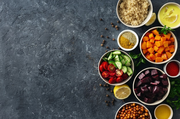 Zestaw zdrowych wegetariańskich składników do gotowania. przyprawiona ciecierzyca, pieczona dynia i buraki, komosa ryżowa i warzywa.