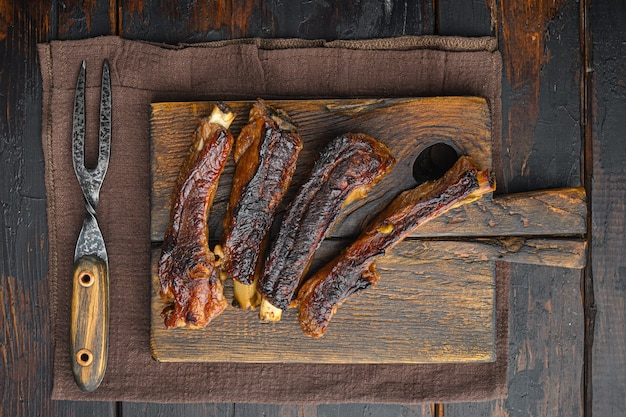 Zestaw żeber wieprzowych z grilla, na drewnianej desce do serwowania, z nożem do grilla i widelcem do mięsa, na starym ciemnym drewnianym stole, widok z góry na płasko