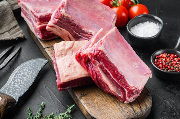 Zestaw żeberek z surowego mięsa, ze składnikami, na czarnym tle kamienia