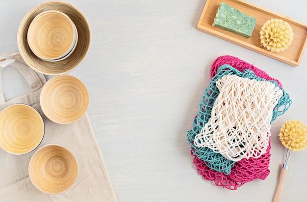Zestaw zero waste. zestaw ekologicznych bambusowych sztućców, bawełniana torba z siateczki, kubek do kawy wielokrotnego użytku, szczotki i butelka na wodę. zrównoważona, etyczna, wolna od plastiku koncepcja
