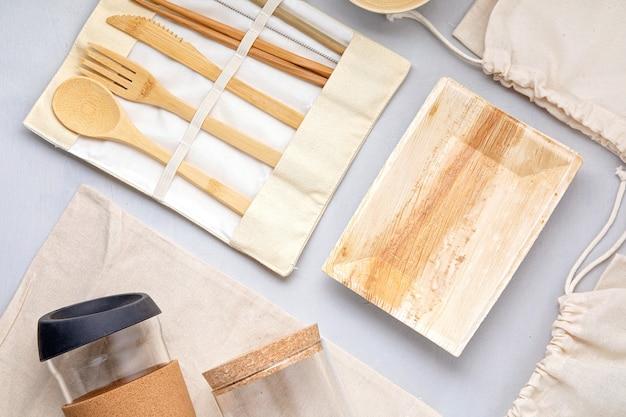 Zestaw zero waste. zestaw ekologicznych bambusowych sztućców, bawełnianej torby z siateczki, kubka do kawy wielokrotnego użytku i butelki na wodę. zrównoważony, etyczny, wolny od plastiku styl życia.