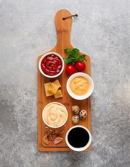 Zestaw zestaw sosów ketchup majonez ser sojowy zielony na desce do krojenia ze składnikami na