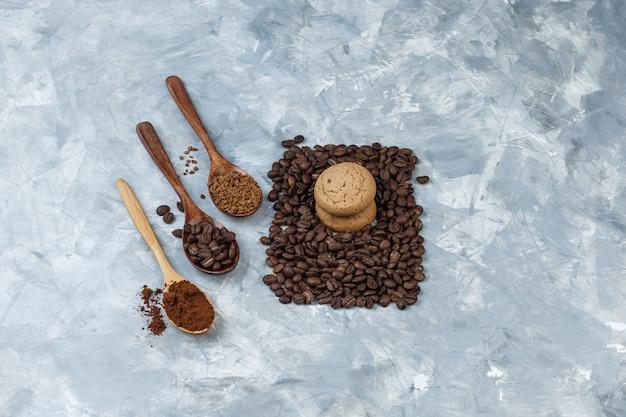 Zestaw ziaren kawy, kawy rozpuszczalnej, mąki kawowej w drewnianych łyżeczkach i ciasteczka na jasnoniebieskim tle marmuru. widok pod dużym kątem.