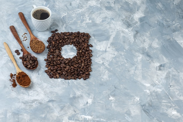 Zestaw ziaren kawy, kawy rozpuszczalnej, mąki kawowej w drewnianych łyżeczkach i filiżankę kawy na jasnoniebieskim tle marmuru. widok pod dużym kątem.