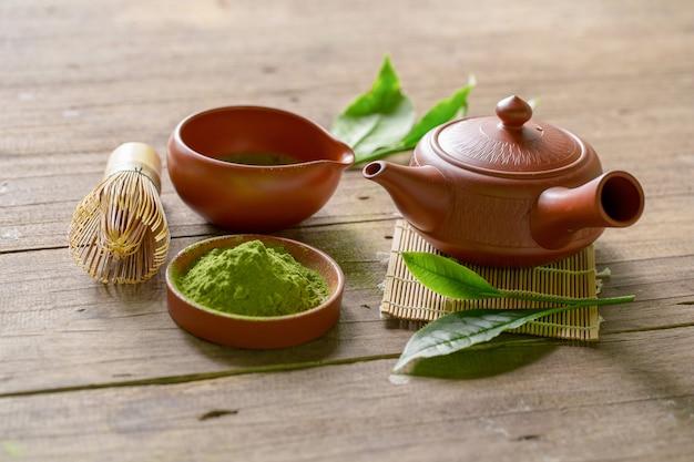 Zestaw zielonej herbaty matcha i japońskiej herbaty. ceramiczny czajniczek i parująca filiżanka na drewnianym tle