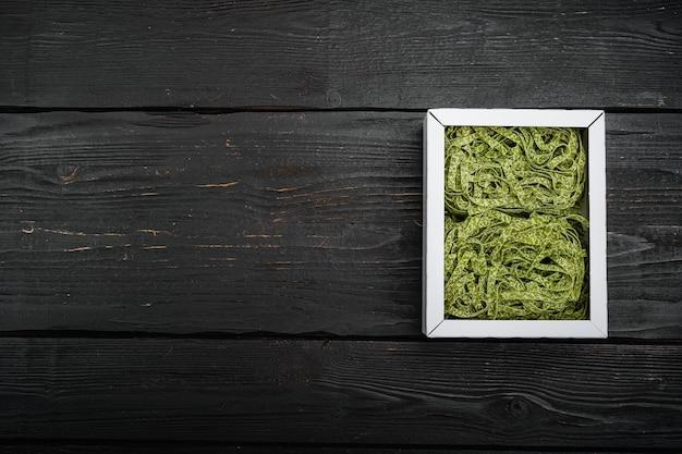 Zestaw zielony makaron tagliatelle surowy szpinak, na tle czarnego drewnianego stołu, widok z góry płasko leżał, z kopią miejsca na tekst