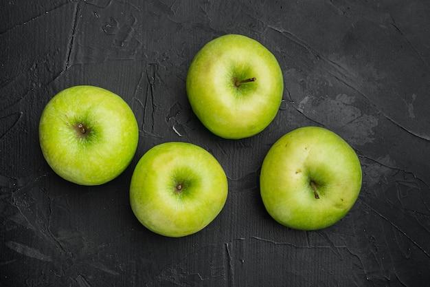 Zestaw zielonych jabłek, na czarnym tle ciemnego kamiennego stołu, widok z góry płaski lay