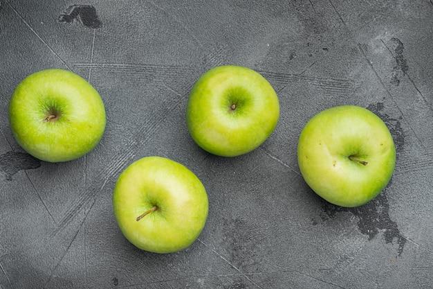 Zestaw zielonych jabłek, na szarym tle kamiennego stołu, widok z góry płaski lay