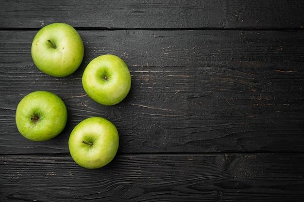 Zestaw zielonych jabłek, na tle czarnego drewnianego stołu, płaski widok z góry, z miejscem na kopię tekstu