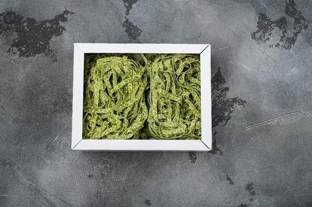 Zestaw zielonych makaronów tagliatelle, na szarym tle kamiennego stołu, płaski widok z góry, z miejscem na kopię na tekst
