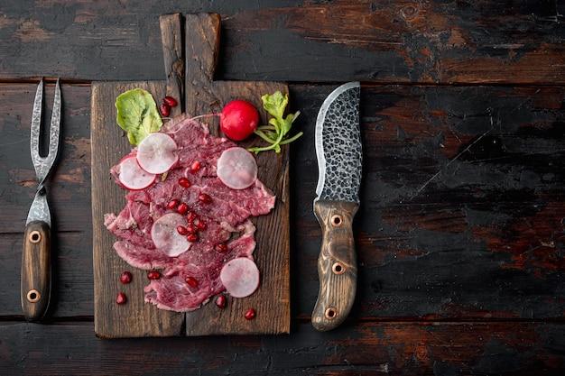 Zestaw zimnych przystawek carpaccio z wołowiny, rzodkiewki i granatu, na drewnianej desce do serwowania, na starym ciemnym drewnianym stole