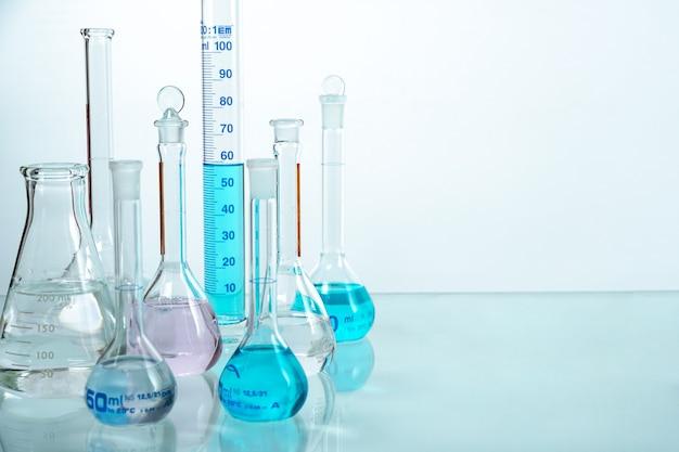 Zestaw zlewek ze szkła laboratoryjnego wypełnionych płynem w innym kolorze z odbiciem na białym