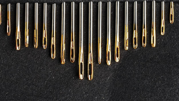 Zestaw złotych igieł na czarnym tle z rzędu.